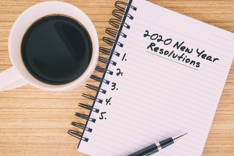 "A journal that says ""2020 New Year Resolutions"" with a numbered list. A cup of black coffee is placed on a table right next to the journal."